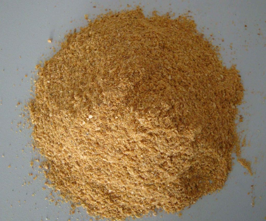 Close up of a pile for corn gluten on a grey counter top